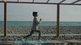 lunges : Young slim woman is working muscles of her legs, hips and buttocks. She is training on sea coast, squating with lunges Stock Footage