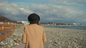 sable : Pensive young lady is strolling on empty beach in sunny weather. She is looking around, her hair is swaying by wind, back view on her body Vidéos Libres De Droits