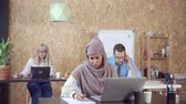 ambience : Hard-working muslim woman working on laptop and with documets at the table. Arabic woman in hijab. Two office workers on the background.