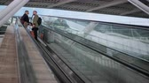chateando : Pair of travelers with luggage are standing on escalator moving down