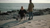 spouses : Woman is sitting in wheelchair on sea coast and holding hand of her husband