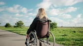 olasılık : Adult disabled woman is driving her wheelchair in park area in sunny day