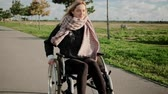 freuen : Cheerful disabled woman is driving her invalid carriage in park, frontal view