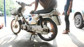 classic : Bangkok, Thailand - May 1, 2016 : Kick start a motorcycle by service man for fix a vintage bike in garage