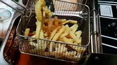 fattening : Slow motion of French fries or chips (potato) deep frying in heat oil for a side dish or snack in fastfood restaurant , unhealthy food or fat concept Stock Footage