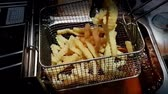 deep fat frying : Slow motion of French fries or chips (potato) deep frying in heat oil for a side dish or snack in fastfood restaurant , unhealthy food or fat concept Stock Footage