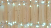 espaço para o texto : Fancy blinker light bulbs or garlands and wreath on wood table for Christmas or New years decoration background, Christmas colorful glowing lights border celebrate with space for add text or picture. 4K, UHD.