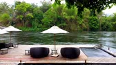 Deck chair or daybeds and umbrellas on waterfront raft in resort near river Kwai Kanchanaburi, Thailand. travel and vacation in Thailand
