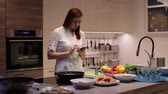 recipe : Young woman using smartphone standing in kitchen at home