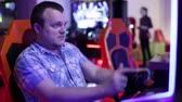 chapéus : Man sits and spins the wheel on the slot machine simulator races Stock Footage