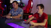 chapéus : The young man and the teenager sitting at the gaming panel, press