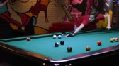 furniture : Teen playing pool billiard, takes aim and hits the ball