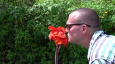 maço : A man sniffing a beautiful red flower Stok Video