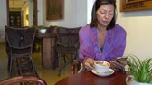cardigã : Woman sitting at table in cafe drinking coffee and using smartphone