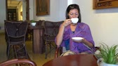 restoran : Woman drinking coffee while sitting at a table in a cafe