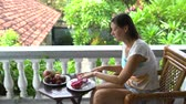 müsli : Woman sitting on the balcony cuts the Pitahaya and eats