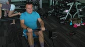 бегун : A man has been rowing Simulator in the gym
