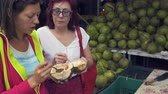 subtropics : Women eat young green coconut on the street