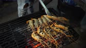 çili : King prawns are fried on the grill. Male hand overturns shrimp using forceps Stok Video