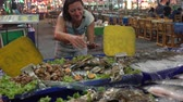 scratchy : The woman takes shells with shellfish from the counter with seafood. Street food