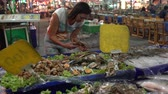 halak : A woman takes a living lobster from the counter with seafood. Street food