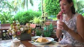 tremer : Woman drinking a milkshake at a restaurant Stock Footage