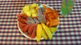 porcelana : On the table is a plate of fruit. Female hand takes papaya with a fork Vídeos