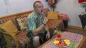 flocos de milho : Man sitting on the couch at home eating fruit and drinking juice Vídeos