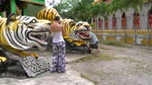пантеры : A woman is taking pictures of a man with a tiger statue.