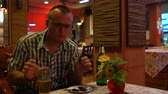 крикет : A man eating a fried scorpion and drinking beer in a Thai restaurant Стоковые видеозаписи