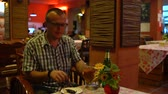 крикет : A man drinks beer and eats a roasted cockroach at a Thai restaurant