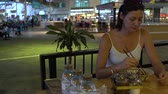 pauzinhos : A woman at the station cafe eating Pad Thai sticks