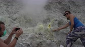 ácido : A man is taking pictures of a woman next to a fumarole on a smartphone