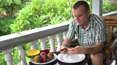 orangejuice : Man sitting on the balcony cleans the Salacca fruit and eats