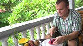 orangejuice : Man sitting on the balcony cleans the Pitahaya fruit and eats