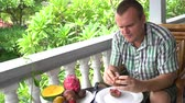 orangejuice : Man sitting on the balcony cleans the mangosteen fruit and eats