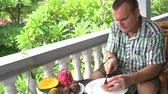 orangejuice : Man sitting on the balcony cleans the passion fruit and eats Stock Footage