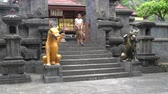 alms : A woman in a long skirt emerges from a Buddhist temple and descends a stone staircase with statues Stock Footage