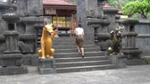 alms : A woman in a long skirt rises to a Buddhist temple on a stone staircase with statues