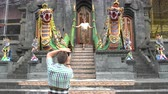 alms : A man takes pictures of a woman on a smartphone in front of the entrance to a Buddhist temple Stock Footage