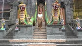 alms : A woman descends the stone staircase with statues in a Buddhist temple