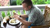 смаковать : A man sitting on a balcony cleans durian with his hands Стоковые видеозаписи