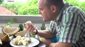смаковать : A man sits on the balcony at the table and eats durian hands