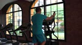 férfias : In the gym, the man has an elliptical exerciser