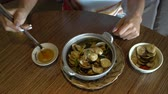 pauzinho : The female hand takes the mussel from the shell with chopsticks and dips it into the sauce Stock Footage