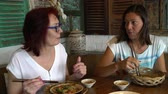 Çin yemek çubukları : Women eat seafood and chicken skewers at the restaurant and talk