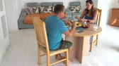 Woman and man eat sitting at table at home