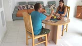 Woman and man are sitting at the table at home having lunch and talking Stockvideo