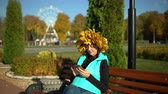 A woman with a maple wreath on her head sits on a park bench and uses a smartphone