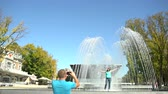 Man shoots woman at the fountain Stock Footage